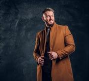 Красота ` s людей, сезонная мода Стильно одетый человек в пальто demi-сезона усмехаясь и выглядя косой Фото студии стоковое фото
