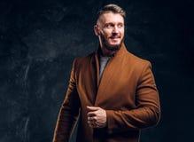 Красота ` s людей, сезонная мода Стильно одетый человек в пальто demi-сезона усмехаясь и выглядя косой Фото студии стоковые фотографии rf