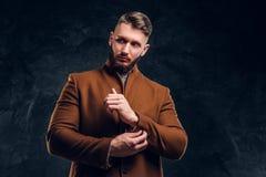 Красота ` s людей, сезонная мода Стильно одетый человек в пальто demi-сезона застегивая вверх по его рукаву Фото студии стоковые изображения rf