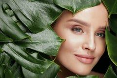 красотка естественная Красивая сторона женщины в зеленых листьях Стоковые Изображения
