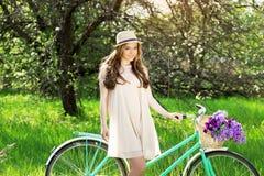 красотка совершенная Горизонтальная съемка красивой молодой женщины в платье и шляпе смотря камеру и усмехаясь пока стоящ с велос Стоковое Изображение