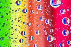 Красочная абстрактная предпосылка воды падает на стекло с цветами радуги Стоковая Фотография RF