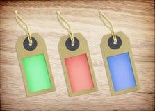 Красочная бумага бирки на деревянной предпосылке текстуры Стоковые Изображения