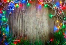 Красочная гирлянда рождества освещает на деревянной деревенской предпосылке деревянное украшений рождества экологическое стоковая фотография