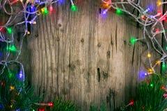 Красочная гирлянда рождества освещает на деревянной деревенской предпосылке деревянное украшений рождества экологическое стоковые изображения rf