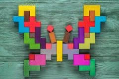 Красочная деревянная головоломка в форме бабочки на зеленой деревянной предпосылке Стоковое Фото