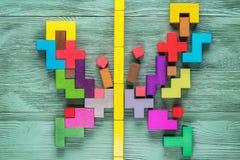 Красочная деревянная головоломка в форме бабочки на зеленой деревянной предпосылке Стоковое фото RF