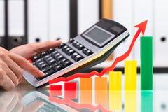 Красочная диаграмма около предпринимателя используя калькулятор стоковая фотография rf