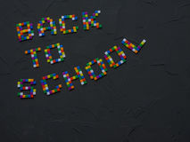 Красочная ЗАДНЯЯ ЧАСТЬ К словам ШКОЛЫ с частью подсказок карандаша цвета показанных в рамке задняя школа принципиальной схемы к Стоковое Фото