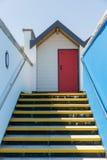 Красочная красная дверь, при каждое одно будучи пронумерованным индивидуально, белых пляжных домиков на солнечный день, взгляд см стоковая фотография