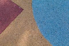 Красочная красная, желтая и голубая резиновая поверхность пола спортивной площадки Wetpour Стоковое фото RF