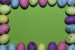 Красочная рамка яйца конфеты с зеленым космосом экземпляра стоковое изображение
