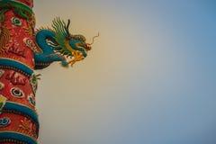 Красочная статуя китайского дракона обернутая вокруг красного штендера залива Стоковые Фото