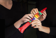 Красочная труба и 4 руки женщины принимая его стоковые фото