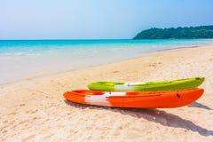 Красочная шлюпка каяка на пляже и море Стоковые Фото