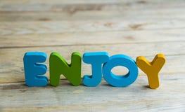 Красочное деревянное слово наслаждается на woodne floor1 Стоковые Фото