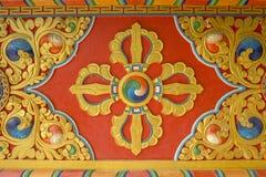 Красочное яркое красное желтое голубое буддийское изображение vajra на стене виска изображения священнейшие стоковая фотография