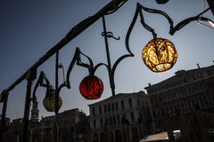 Красочные лампы на богато украшенных перилах в Венеции, Италии, с венецианскими домами на заднем плане Стоковое Фото