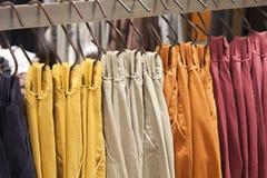 Красочные брюки вися показ на шкафе в магазине стоковое изображение
