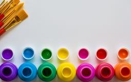 Красочные бутылки и кисти краски на белой предпосылке с космосом экземпляра, взгляд сверху/искусствами и концепцией предпосылки р Стоковые Фотографии RF