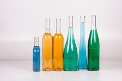Красочные бутылки и стекла на белой предпосылке Стоковое Изображение RF