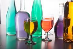 Красочные бутылки и стекла на белой предпосылке Стоковая Фотография RF