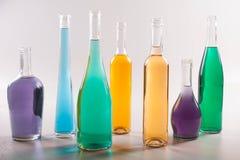 Красочные бутылки и стекла на белой предпосылке Стоковое Фото