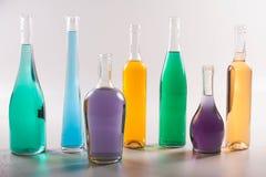 Красочные бутылки и стекла на белой предпосылке Стоковое фото RF