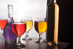 Красочные бутылки и стекла на белой предпосылке Стоковая Фотография