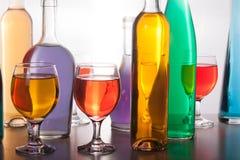 Красочные бутылки и стекла на белой предпосылке Стоковые Фото