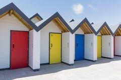 Красочные двери голубого, желтой и красной, при каждое одно будучи пронумерованным индивидуально, белых пляжных домиков на солнеч Стоковое Фото