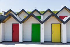 Красочные двери желтой, красной и зеленой, при каждое одно будучи пронумерованным индивидуально, белых пляжных домиков на солнечн Стоковое Фото