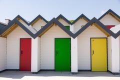 Красочные двери желтой, красной и зеленой, при каждое одно будучи пронумерованным индивидуально, белых пляжных домиков на солнечн Стоковое фото RF