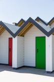 Красочные двери зеленой и красной, при каждое одно будучи пронумерованным индивидуально, белых пляжных домиков на солнечный день Стоковые Изображения