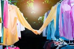 Красочные влажные одежды вися на стальной веревке для белья для сушить жарой солнца Сладкие пары концепции рубашек Счастливый стоковое фото