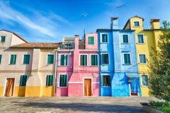 Красочные дома в острове Burano с пасмурным голубым небом около Венеции, Италии Популярное и известное туристское место Стоковое Изображение