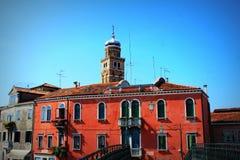 Красочные жилые дома и колокольня церков Сан Pietro Martire в лагуна острове Burano, Венеции Стоковое Изображение
