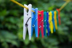 Красочные зажимки для белья вися на веревке для белья Стоковое Фото