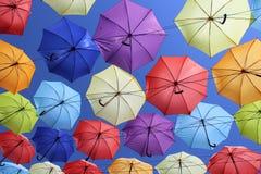 Красочные зонтики летая в голубое небо стоковые фото