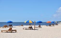 Красочные зонтики на деревянных салонах на пляже Стоковая Фотография RF