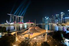 Красочные здание небоскреба Сингапура и лазер показывают в ноче a стоковое фото