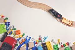 Красочные игрушки детей: пластичные инструменты игрушки, болты, гайки, автомобиль, поезд с деревянным рельсом на белой предпосылк Стоковые Изображения RF