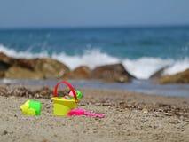 Красочные игрушки пляжа, ведро и лопаткоулавливатель, в песке с видом на море стоковое фото