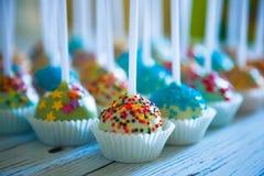 Красочные испеченные cakepops на белой деревянной предпосылке Стоковые Изображения RF