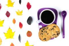 Красочные листья падения и фиолетовая кофейная чашка с поддонником, ложкой изолированной на белой предпосылке Стоковое Изображение RF