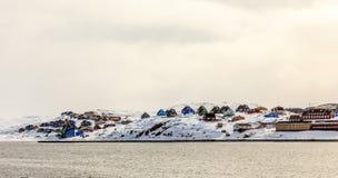 Красочные кабины на холме предусматриванном в снеге, городе Aasiaat Стоковое Изображение