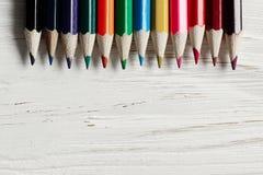 Красочные карандаши на белой деревенской деревянной предпосылке творческое bor стоковые изображения rf
