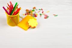 Красочные карандаши и ручки войлок-подсказки в желтом случае карандаша, красочных зажимах notepapers, бумажных и ногтях канцелярс Стоковое Изображение