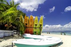 Красочные каяки на тропическом белом песочном seashore с пасмурной предпосылкой голубого неба Стоковые Изображения