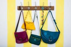 Красочные кожаные сумки вися на деревянном шкафе стоковое изображение rf